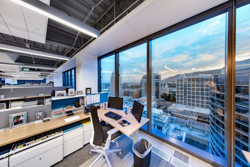 Employee desk with low cubicle walls and floor to ceiling windows looks out over local buildings at sunrise