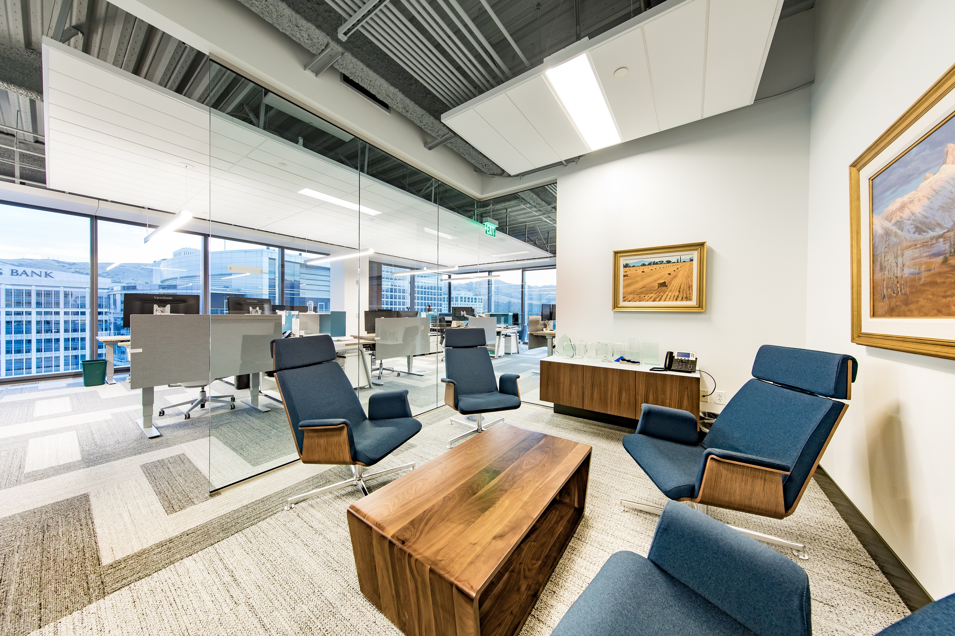 An interior meeting room has glass walls and four padded, semi-reclined chairs surrounding a wooden coffee table.