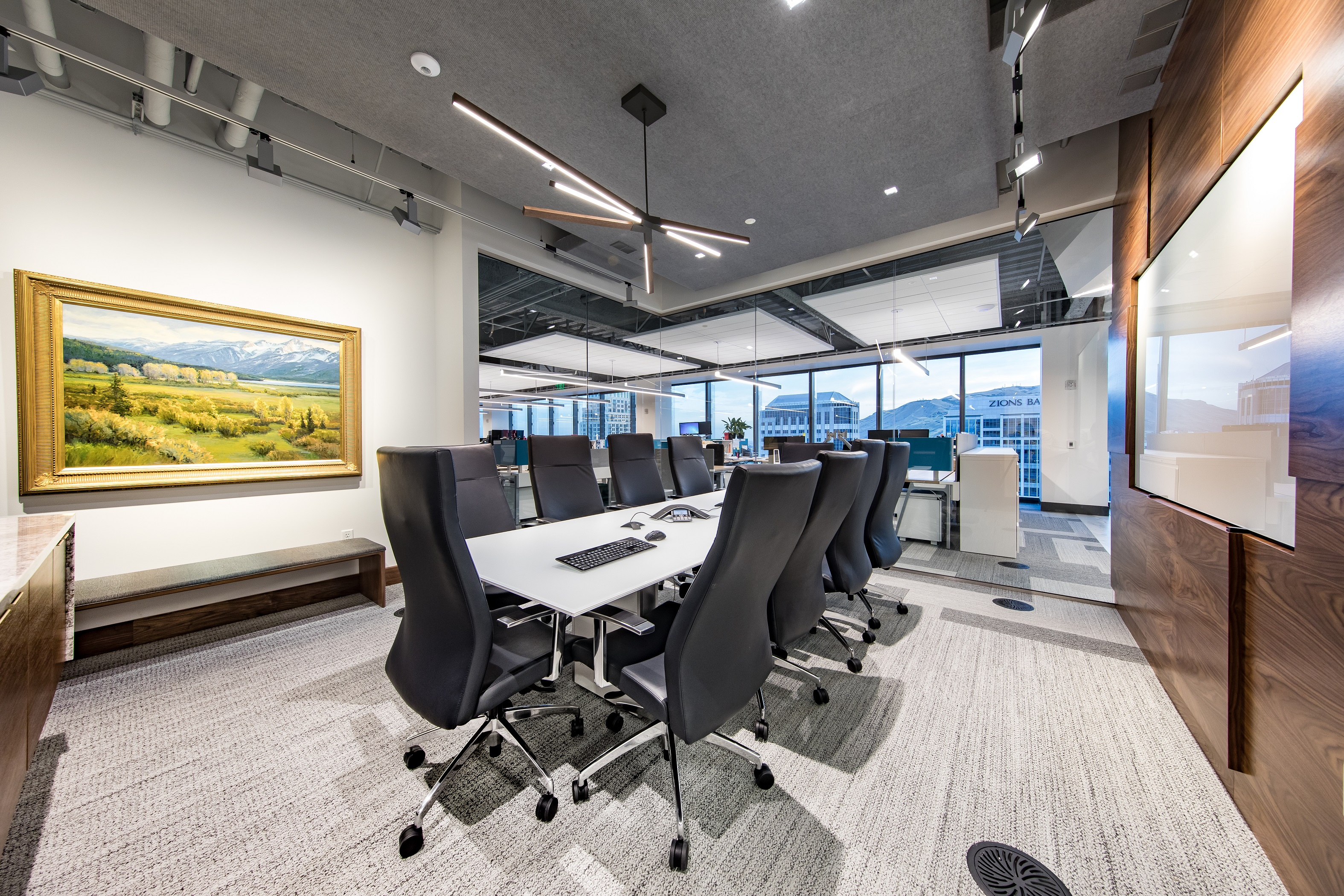 The modern, new board room in Bonneville's headquarters has two glass walls, one textured wood wall featuring an inset, glass white board, and an illuminated wall featuring a Utah landscape painting.