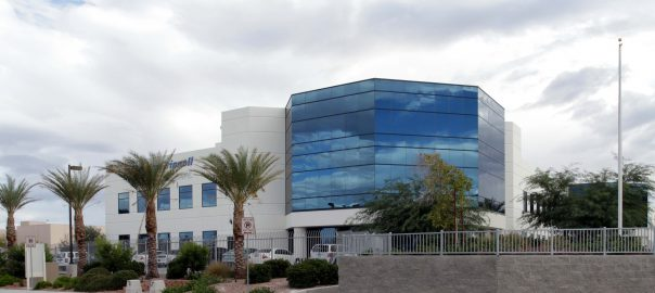 Outside view of Pama Lane industrial building showing glass front, palm trees in front of cloudy sky